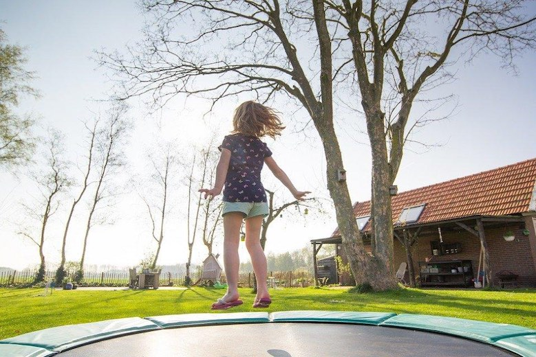 girl on trampoline in backyard